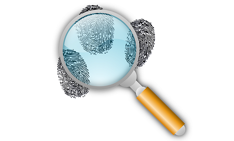 Fingerprints seen through a magnifying glass to represent the investigation of Notes features and mystery documents. For support REW Computing offers services in eDiscovery, project management and IBM Lotus Notes support for Newmarket, Toronto, the GTA, and Ontario, Canada.